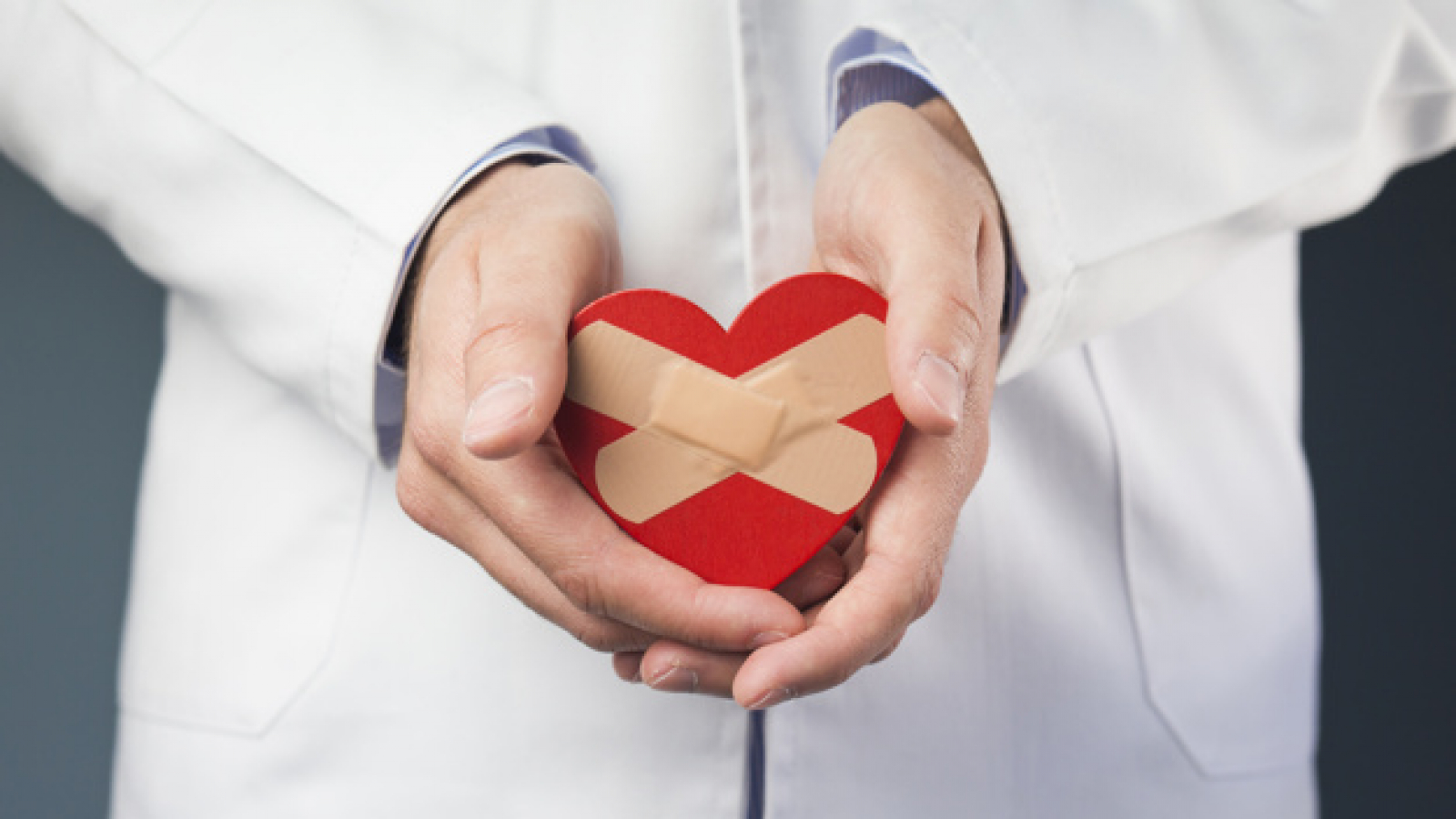 close-up-doctor-s-hand-holding-red-heart-with-crossed-bandages_23-2148050573