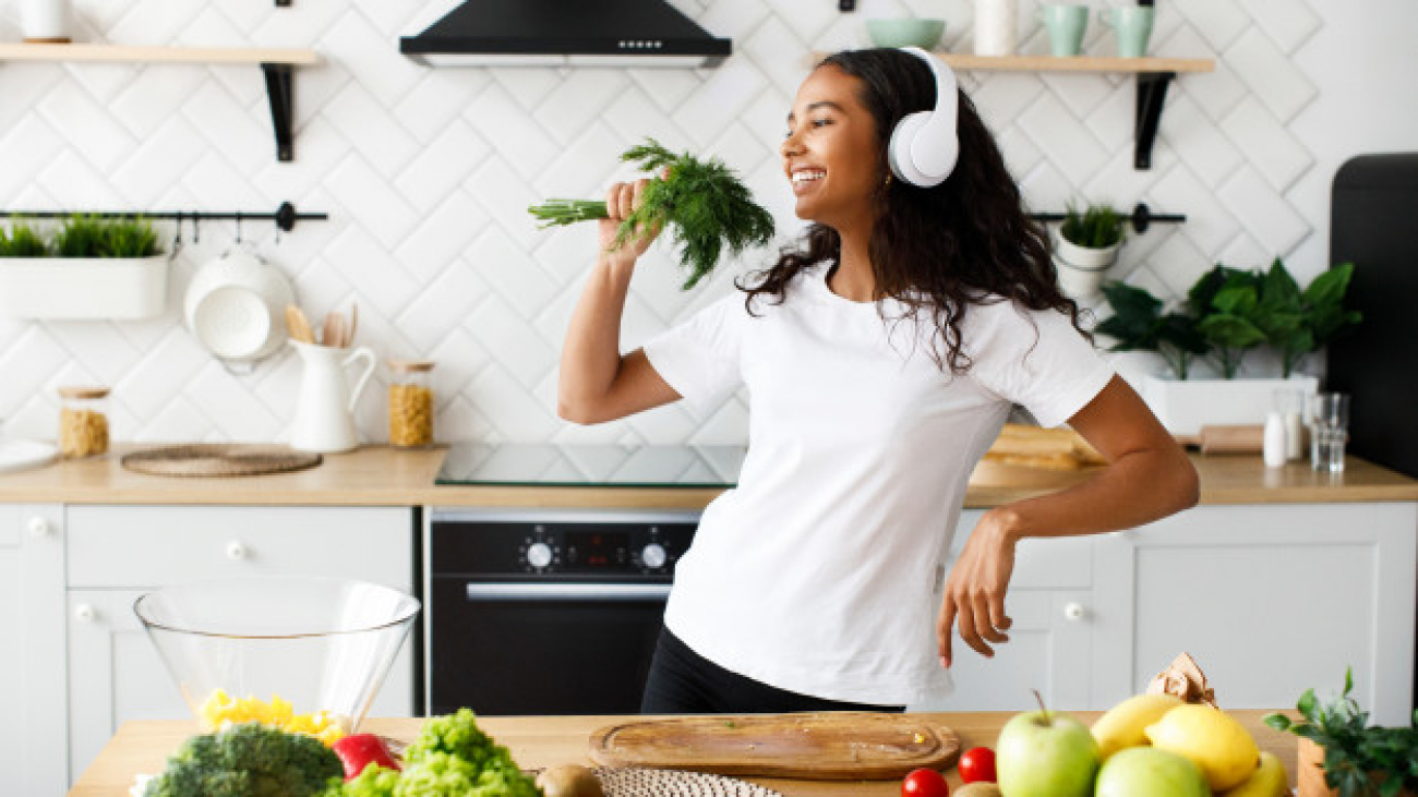 good-looking-mulatto-woman-big-headphones-is-smiling-pretending-like-she-is-singing-greenery-near-table-with-fresh-vegetables-fruits_8353-10267