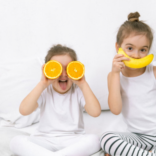 happy-two-cute-children-playing-with-fruits-vegetables_169016-1853