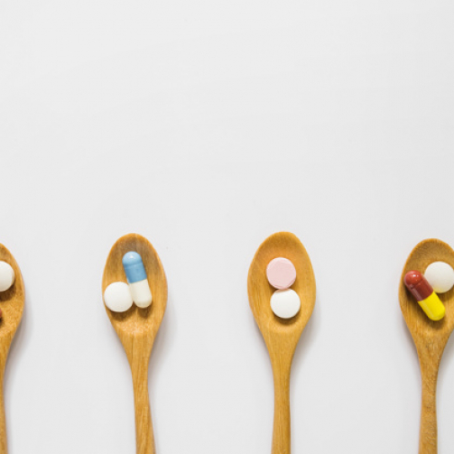 overhead-view-wooden-spoons-with-pills-isolated-white-background_23-2147883817