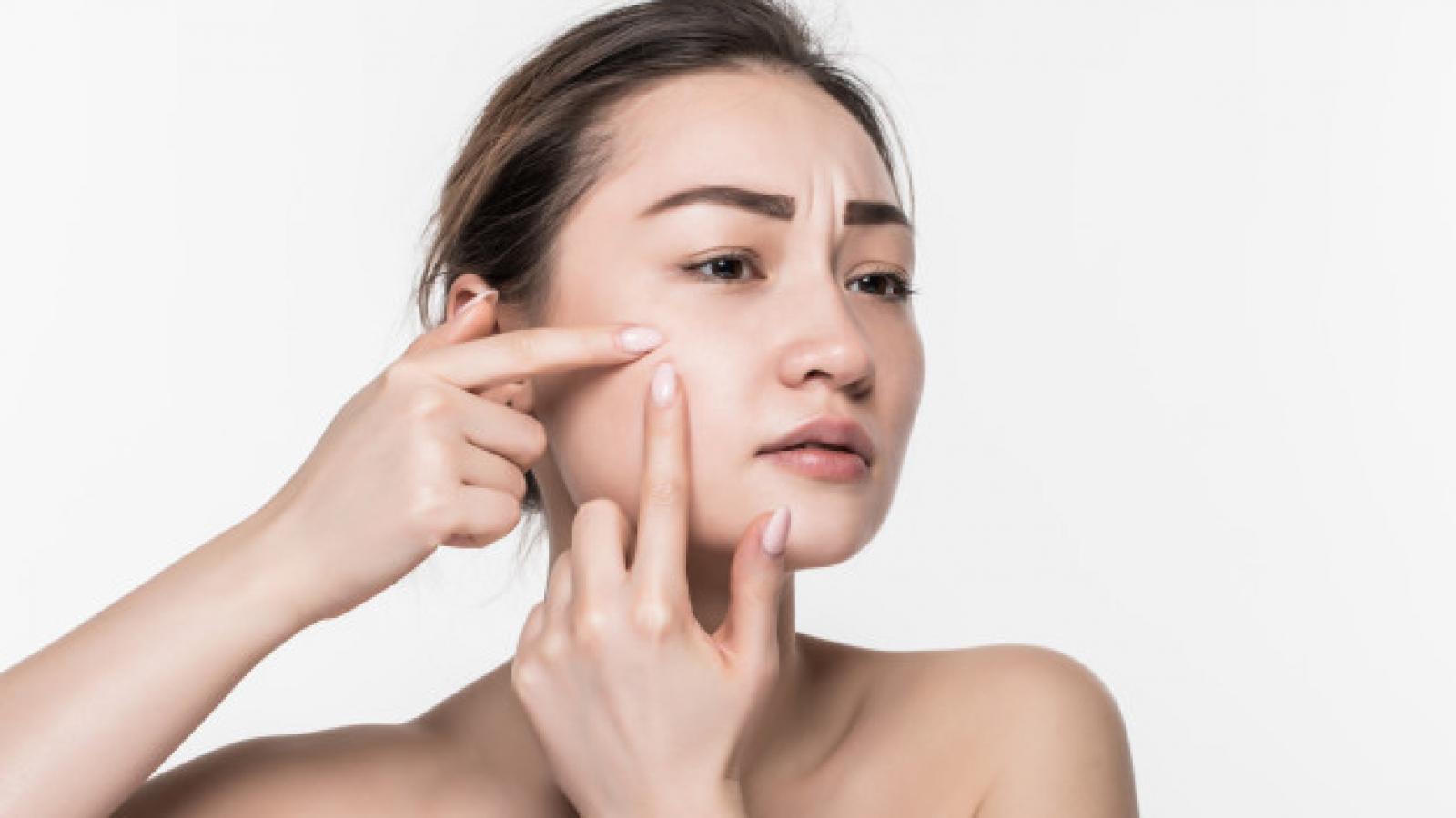 portrait-young-attractive-woman-touching-her-face-looking-acne-isolated-white-wall_231208-1025