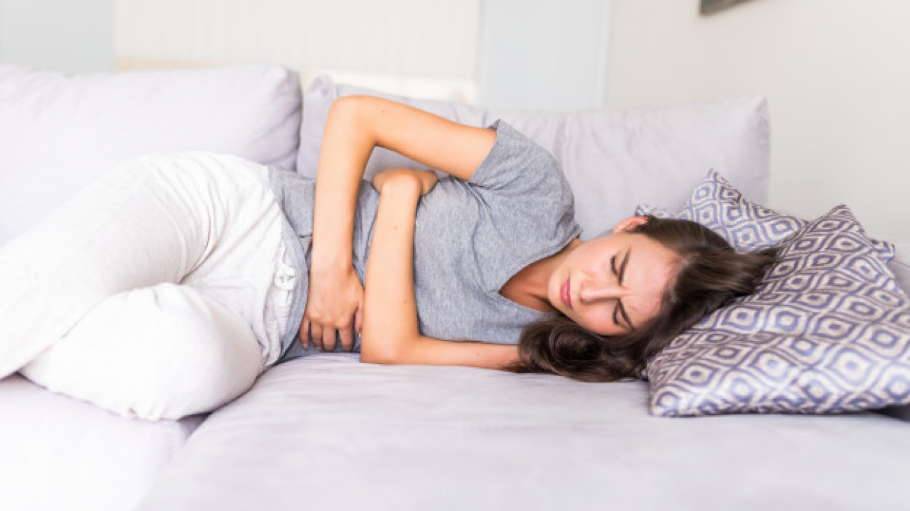 young-woman-haviing-abdominal-pain-because-menstruation-lying-couch-holding-her-stomach_231208-689